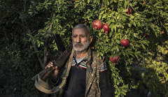 A local resident Anushavan (62) stands in a pomegranate garden in the yard of his house. He is holding an old Kalashnikov assault rifle, which he has kept from the first Karabakh war.  Ukhtasar village.